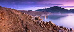South Holston Dawn (Greg Booher) Tags: road longexposure morning panorama usa lake reflection water fog clouds canon bristol landscape eos rebel early twilight rocks purple streetlights tennessee earlymorning dirt sullivan 1855 efs xsi easttennessee tiretracks southholstonlake nothdr 450d northeasttennessee southholstondam fogonwater gregbooher mygearandme mygearandmepremium flickrstruereflection1