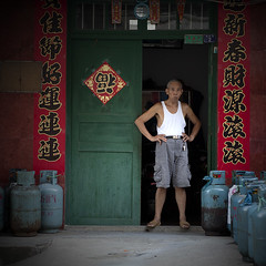 Gassed (Michael Steverson) Tags: china door man canon asian tank yangshuo chinese tshirt gas chinadigitaltimes 5d vendor shorts propane wifebeater guangxi markii couplets ef2470f28lusm
