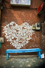 A white heart-shaped painting on brick wall and in front of it is a long blue wooden bench.