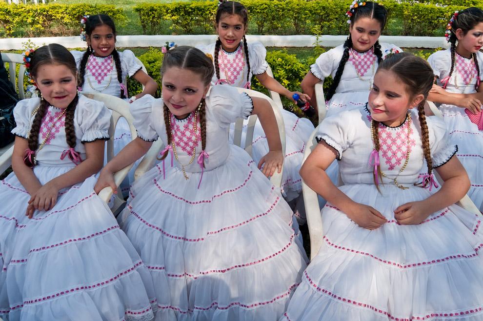 Niñas bailarinas visten ropas típicas de diseños influenciados por la moda europea antigua, durante la espera para la participación en los actos culturales del Festival del Licor. (Elton Núñez)
