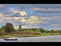 behind the watergate - a windmill and a boat (Wim Koopman) Tags: sky holland mill water netherlands windmill dutch clouds river photography boat photo nikon ship gull stock nederland ramparts motorboat stockphoto waal stockphotography gorinchem d90 wpk
