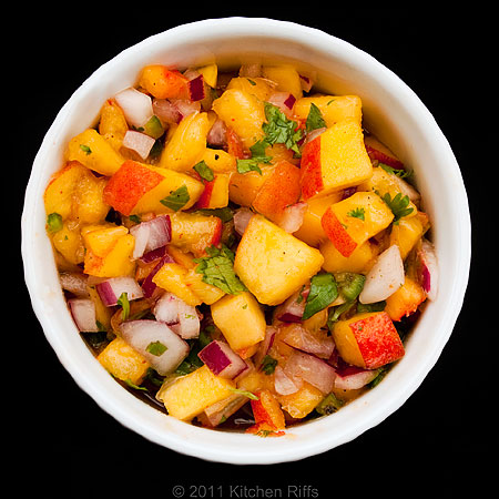 Peach salsa in white ramekin on black background, overhead view