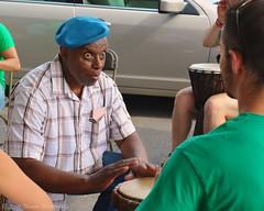 Drum Teacher (Scottwdw) Tags: travel summer vacation people newyork man look fairgrounds intense eyes hands nikon looking drum teacher cap syracuse drummer vr newyorkstatefair nysf d700 yourphototips panafricanvillage 2803000mmf3556 scottthomasphotography