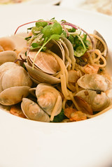 A photo of a seafood and olive oil pasta on a white circular plate.
