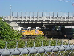 A container freight emerges from the shade of the new 99e viaduct