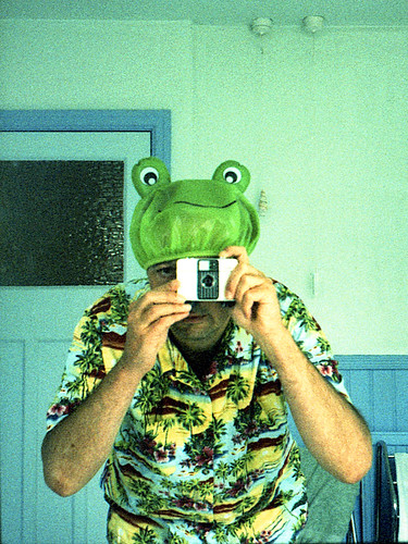 reflected self-portrait with Ricoh Auto-Half camera and frog shower cap by pho-Tony