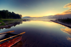Rising sun (- David Olsson -) Tags: morning mist lake nature water fog clouds sunrise reflections landscape early haze nikon rocks raw sweden jetty tripod sigma calm lifeboat rowboat 1020mm tranquil hdr brygga vrmland cameraraw redboat lakescape rescueboat gapern photomatix d5000 floatingpier davidolsson