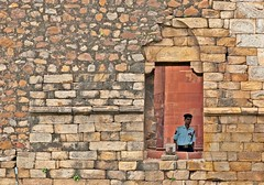 The Man in the Window (Shubh M Singh) Tags: light red portrait people india yellow architecture ancient nikon sandstone alone peace walk delhi muslim islam north historical 300 d200 minimalism punjab nikkor solitary f4 qutub minar afs islamic qutb qutab mehrauli nikonstunninggallery
