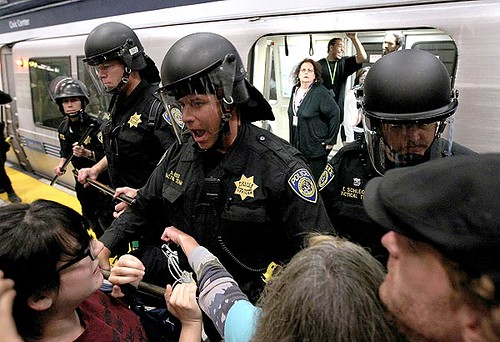 Bay Area Rapid Transit police push back demonstrators who are trying to keep a train from leaving the Civic Center station in San Francisco.