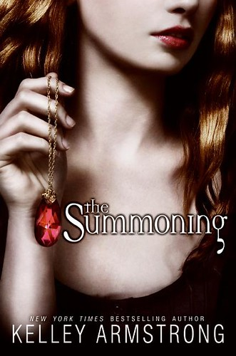Cover for The Summoning (a pale person holding a gemstone in a raised hand)