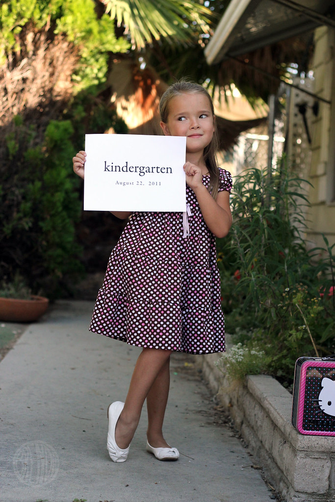 "Young girl wearing a dress posing for a photo while holding a sign that says ""kindergarten"""