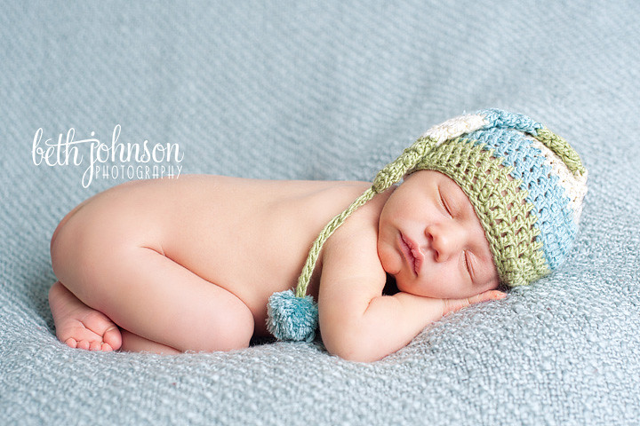 newborn baby boy in blue green and cream elf hat