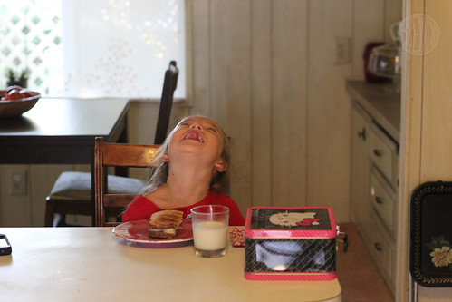 girl sitting at the kitchen table laughing while eating breakfast
