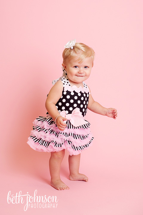 baby girl standing on pink backdrop in studio