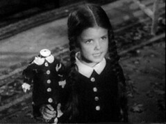 Lisa Loring as Wednesday Addams holding a headless doll.