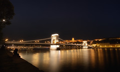 By The Danube (TheFella) Tags: longexposure bridge people moon slr castle night digital photoshop canon stars eos photo high waiting couple europe hungary dynamic suspension budapest lion palace unescoworldheritagesite unesco chain nighttime photograph processing slowshutter lions dslr duna range danube hdr highdynamicrange buda pest royalpalace magyarorszg lnchd riverdanube budacastle chainbridge royalcastle postprocessing 500d szchenyi szchenyilnchd photomatix szchenyichainbridge budavripalota republicofhungary kirlyivr istvnszchenyi kirlyipalota thefella conormacneill chainsuspension thefellaphotography
