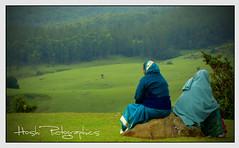 広大な草原を背景に座る二人の女性