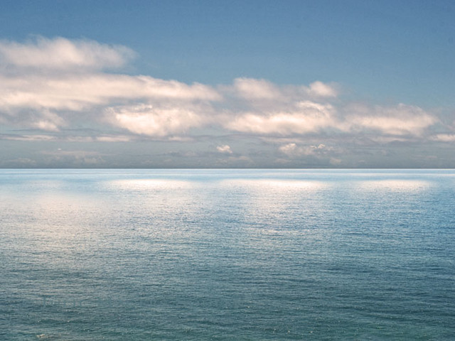 The Pacific Ocean catches the soft light of late afternoon from a cloud filled blue sky.