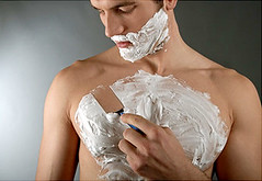 young man with shaving cream on his face and chest shaving his chest hair with a disposable razor