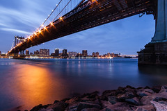 A River Runs Through It (Mihai Andritoiu) Tags: city nyc longexposure bridge blue sunset sky urban bw usa ny newyork motion blur water skyline brooklyn night clouds america canon buildings river stars photography lights evening us photo rocks cityscape unitedstates sundown suspension very stones manhattan tripod under dumbo overpass wideangle down super east filter hour transportation infrastructure ultra graduated eosrebel starbursts uwa 500d canonefs1022mmf3545usm gnd vle neutraldensity canonefs10223545usm canoneos500d concordians t1i outstandingromanianphotographers
