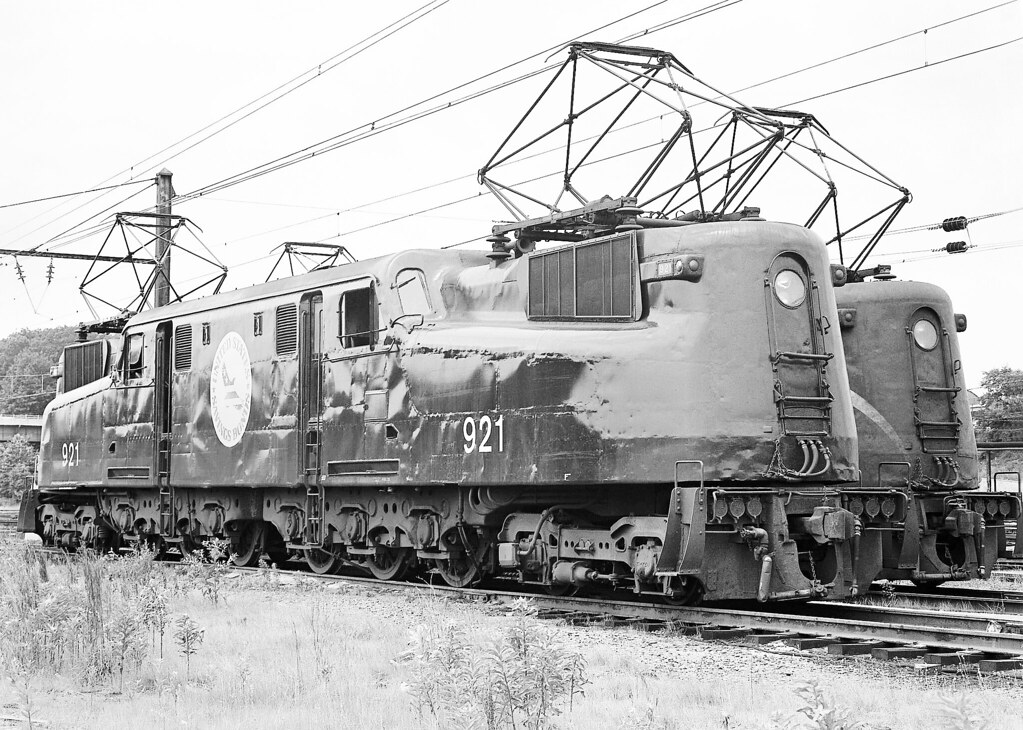 """Amtrak GG-1 electric locomotive # 921, (""""United States Savings Bonds,"""" decal Locomotive) along with another are seen on the ready tracks in the Ivey City Railroad Yard at Washington, D.C., June 1976"""