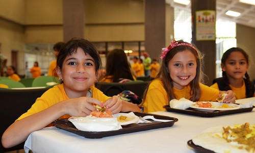 Three children enjoy lunch freshly prepared and served on-site by a food service management company at the Inter Metro Summer Recreation Program in San Juan, Puerto Rico.
