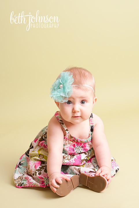 six month old baby girl in photography studio green backdrop