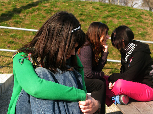 A girl sitting all alone in the corner of a playground, with two girls in the background gossiping about her.