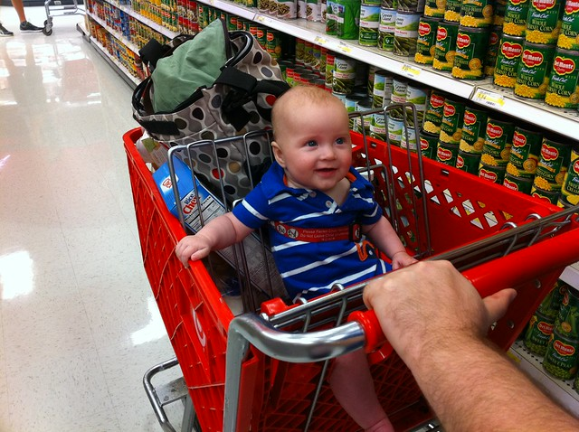 Sitting up like a big boy in the grocery cart.