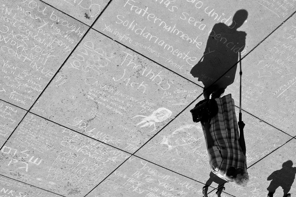 a black and white image of an old lady at the jack layton chalk memorial in toronto's nathan phillips square city hall