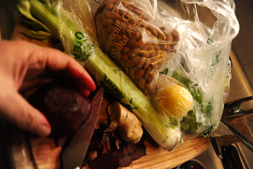 Cutting a beet stains fingers red; making a salad on a cutting board in the sink, shelled almonds, celery, celantro, lemon, veggies in plastic bags, Broadview, Seattle, Washington, USA by Wonderlane