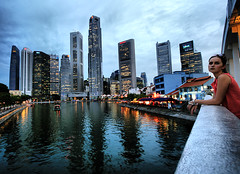 Watching Singapore (` Toshio ') Tags: city bridge woman reflection building water girl beauty architecture clouds island evening harbor boat singapore asia downtown paradise cityscape restaurants rail ripples bluehour boatquay centralbusinessdistrict southbridge toshio
