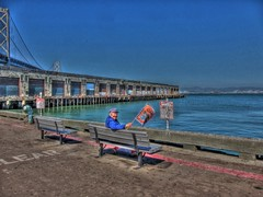 Sitting by the Dock of the Bay (Walker Dukes) Tags: sanfrancisco california bridge pink blue sea orange woman black green water rotting port canon bench oakland pier baseball decay flag gray mature attractive handheld eastbay hdr pennant photomatix tonemapping canons95
