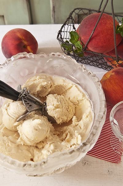 Amazing Amaretto and Fresh Peach Frozen Greek Yogurt in a bowl with ice cream scoop