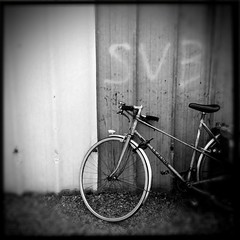 A Memory Of What Was (Shoot Too Kill) Tags: old light blackandwhite white black blur france bike bicycle wall writing vintage handle lights different bell spokes wheels transport shift oldschool retro chain odd riding torch cycle oil brakes dreamy pedals bags flooring tilt gears padlock leaning saddle pedal gravel handlebars lever iphone pushbike tiltshift spooks lejeune mudguard hipstamatic