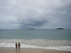 a couple on the beach and a storm over an island in the horizon. (atramos) Tags: brazil woman hot beach florianópolis stock bikini sights pac ingleses darktones
