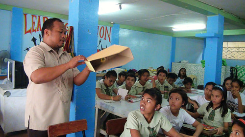 Zapatera Elementary School teacher-in-charge Ronald Navarro shows to grade schoolers a file organizer created from trash. (Tashuana Alemania)