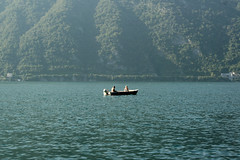 Sitting on the Water (Ben F McManus) Tags: world life trees houses friends light sea wild two house lake como mountains tree nature water boat frozen still couple sitting peace married natural image wildlife pair calm hills around sat capture calmness