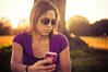 Herself (Proleshi) Tags: summer portrait woman sunlight apple girl sunglasses 50mm golden model dof purple bokeh naturallight hour iphone intheshade goldlight underthetree d300s 50mm14afs sunlightthroughhair proleshi jamaljosephs