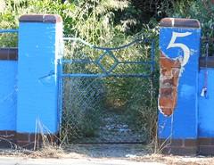 Fraction (mikecogh) Tags: overgrown weeds gate peeling 5 bricks plaster richmond number fraction cobaltblue address