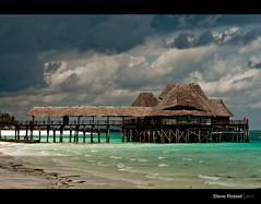 Clouds Over Paradise (Steve Rosset) Tags: ocean africa wood travel roof sea vacation storm building beach water june clouds geotagged tanzania seaside sand paradise escape african turquoise vibrant traditional straw resort adventure exotic coastal tropical zanzibar 2011 visipix geoafrica