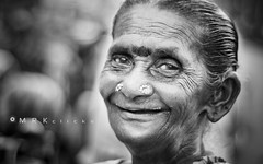 The smile of a stranger (MRK Clicks) Tags: street bw india lady happy 50mm blackwhite nikon bokeh country streetphotography streetportrait stranger outoffocus oldlady indians f2 pulse chennai mrk parrys mrkclicks bestof2011 streetsmile 10best2011