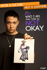 A young, unsmiling Latino man holds up a picture of a costume of a sombrero-wearing white person riding a donkey. The poster reads We're a culture, not a costume. This is not who I am and it is not okay.