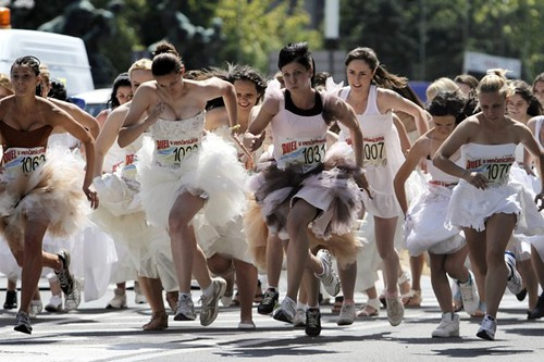 women in bridal gowns running toward a finish line