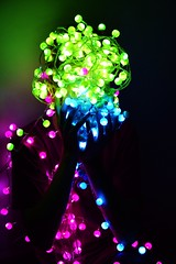 Mask (BornMaimouna) Tags: christmas pink blue light boy tree green colors electric wall night reflections dark lights colorful long exposure neon sitting glow shadows shine mask bright circles balls projection covered messy electricity teenager glowing fairylights shining tangled