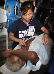 Thanh Dinh, a registered nurse working with Project Hope, listens to a mans heartbeat (U.S. Embassy Jakarta, Indonesia) Tags: navy papuanewguinea usnavy lae projecthope pacificpartnership2011 medicalcommunityservice malahang