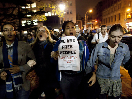 Occupy Wall Street demonstrators march pass city hall after cops raided the encampment at Zuccotti Park evicting hundreds of anti-capitalist campers. The crackdown is taking place nationwide. by Pan-African News Wire File Photos