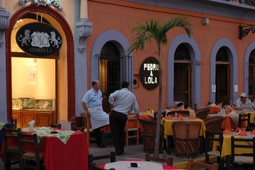 Two business men chatting, Pia Gioielli jewelers lion sign, a waiter from Pedro & Lola restaurant, set tables, palm tree, customers, Machado Square, Centro Historico, Sinaloa, Mexico