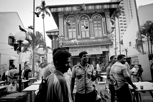 Men watching a public TV broadcast. Little India, Singapore