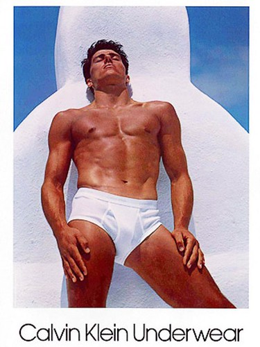 1982 Calvin Klein ad with Tom Hintnaus wearing nothing but a pair of white briefs with his eyes closed against a white and blue background